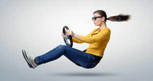 Jeune belle fille dans la voiture de conducteur de lunettes de soleil avec une roue image stock