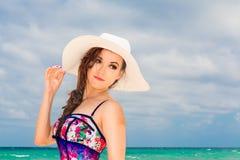 Jeune belle fille dans un chapeau blanc de paille sur la plage d'un trop Photos libres de droits