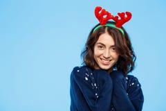 Jeune belle fille de brune dans des andouillers knited de renne de chandail et de Noël souriant au-dessus du fond bleu Image stock