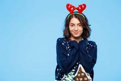 Jeune belle fille de brune dans des andouillers knited de renne de chandail et de Noël souriant au-dessus du fond bleu Photographie stock libre de droits