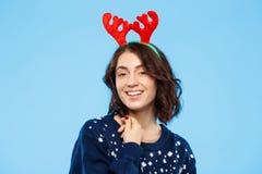 Jeune belle fille de brune dans des andouillers knited de renne de chandail et de Noël souriant au-dessus du fond bleu Images stock