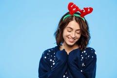 Jeune belle fille de brune dans des andouillers knited de renne de chandail et de Noël souriant au-dessus du fond bleu Photos stock
