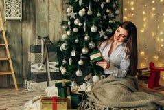 Jeune belle fille de sourire joli blrunette tenant ses cadeaux de Noël se reposant près de l'arbre Photographie stock libre de droits