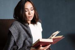 Jeune, belle fille enveloppée dans le livre chaud de lecture de couverture de plaid Photo libre de droits