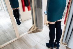 Jeune belle fille essayant sur la nouvelle robe verte dans la cabine d'essayage dans la boutique photographie stock