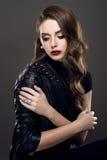 Jeune belle fille fascinante de style de roche dans la veste en cuir noire avec des accessoires sur le fond gris-foncé Images stock