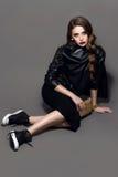 Jeune belle fille fascinante de style de roche dans la veste en cuir noire avec des accessoires sur le fond gris-foncé Images libres de droits