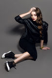 Jeune belle fille fascinante de style de roche dans la veste en cuir noire avec des accessoires sur le fond gris-foncé Image stock