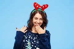 Jeune belle fille gaie de brune dans des andouillers knited de renne de chandail et de Noël souriant au-dessus du fond bleu Photographie stock