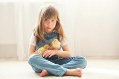 Jeune belle fille, jouant avec le petit poussin nouveau-né à la maison photographie stock