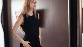 Jeune belle fille joyeuse blonde regardant dans le miroir, lissant la robe clips vidéos