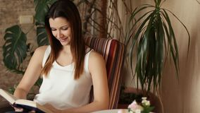 Jeune belle fille lisant un livre se reposant dans une chaise Femme attirante souriant tout en lisant un livre Émotions positives banque de vidéos