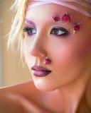 Jeune belle fille, maquillage pourpre élégant et roses sur le visage Images stock
