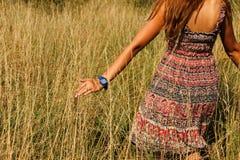 Jeune belle fille marchant dans le champ et la main de courses par la haute herbe sèche à l'été Image libre de droits
