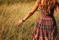 Jeune belle fille marchant dans le champ et la main de courses par la haute herbe sèche à l'été Photographie stock libre de droits