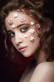 Jeune belle fille nue romantique avec les fleurs blanches sur son visage et les boucles molles sur le fond foncé Images libres de droits