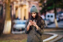 Jeune belle fille occasionnelle invitant son téléphone portable sur la rue de ville de ressort Photo stock