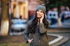 Jeune belle fille occasionnelle invitant son téléphone portable sur la rue de ville de ressort Photos stock