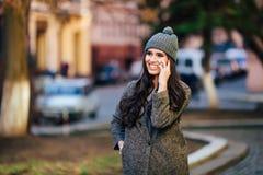 Jeune belle fille occasionnelle invitant son téléphone portable sur la rue de ville de ressort Photographie stock libre de droits