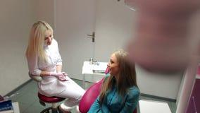 Jeune belle fille parlant avec son dentiste dans le bureau dentaire banque de vidéos