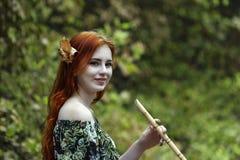 Jeune belle fille rousse dans l'image d'un elfe jouant a photo stock