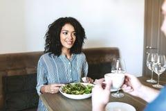Jeune belle fille s'asseyant dans le restaurant avec l'ami et mangeant de la salade Jolie dame d'Afro-américain mangeant de la sa Photos stock