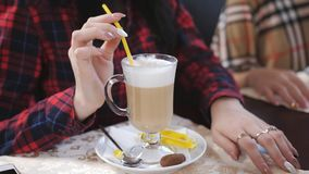 Jeune belle fille s'asseyant dans un café par le latte de fenêtre, de sourire et de boissons banque de vidéos