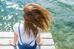Jeune belle fille s'asseyant sur la rivière de jetée sur le fond Photo stock