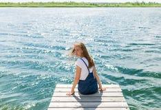Jeune belle fille s'asseyant sur la rivière de jetée sur le fond Photos stock