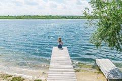 Jeune belle fille s'asseyant sur la rivière de jetée sur le fond Photographie stock libre de droits