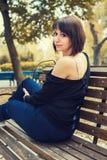 Jeune belle fille s'asseyant sur un banc Photo libre de droits