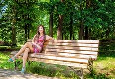 Jeune belle fille s'asseyant sur un banc de parc Photos libres de droits