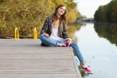 Jeune belle fille s'asseyant sur un pilier Photographie stock