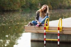 Jeune belle fille s'asseyant sur un pilier Image libre de droits