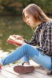 Jeune belle fille s'asseyant sur un pilier Images stock