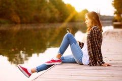 Jeune belle fille s'asseyant sur un pilier Image stock