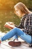 Jeune belle fille s'asseyant sur un pilier Photos stock