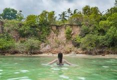 Jeune belle fille sexy dans le bikini marchant dans l'océan à la plage tropicale photos stock