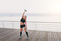 Jeune belle fille sportive avec de longs cheveux blonds dans des écouteurs, écoutant la musique et s'exerçant avec des haltères a Photographie stock
