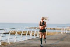 Jeune belle fille sportive avec de longs cheveux blonds dans des vêtements noirs fonctionnant au lever de soleil au-dessus de la  Photo libre de droits