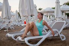 Jeune belle fille sur la plage regardant à la mer images stock