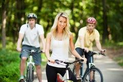 Jeune belle fille sur une bicyclette avec deux hommes à l'arrière-plan Image libre de droits