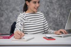 Jeune belle fille travaillant sur l'ordinateur portable au bureau Image libre de droits