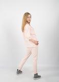Jeune belle fille utilisant les vêtements et les espadrilles roses Image stock