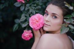 Jeune belle fin de portrait de femme vers le haut de la pose avec les fleurs roses de roses dans un jardin photo libre de droits