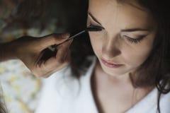 Jeune belle jeune mariée appliquant le maquillage de mariage par l'artiste de maquillage Photos libres de droits