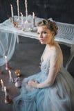 Jeune belle jeune mariée dans la robe de mariage posant dans le studio Photographie stock libre de droits