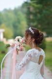 Jeune belle jeune mariée heureuse avec le bouquet de fleur en parc Photographie stock