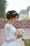 Jeune belle jeune mariée heureuse avec le bouquet de fleur en parc Photographie stock libre de droits