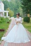 Jeune belle jeune mariée heureuse avec le bouquet de fleur en parc Image stock